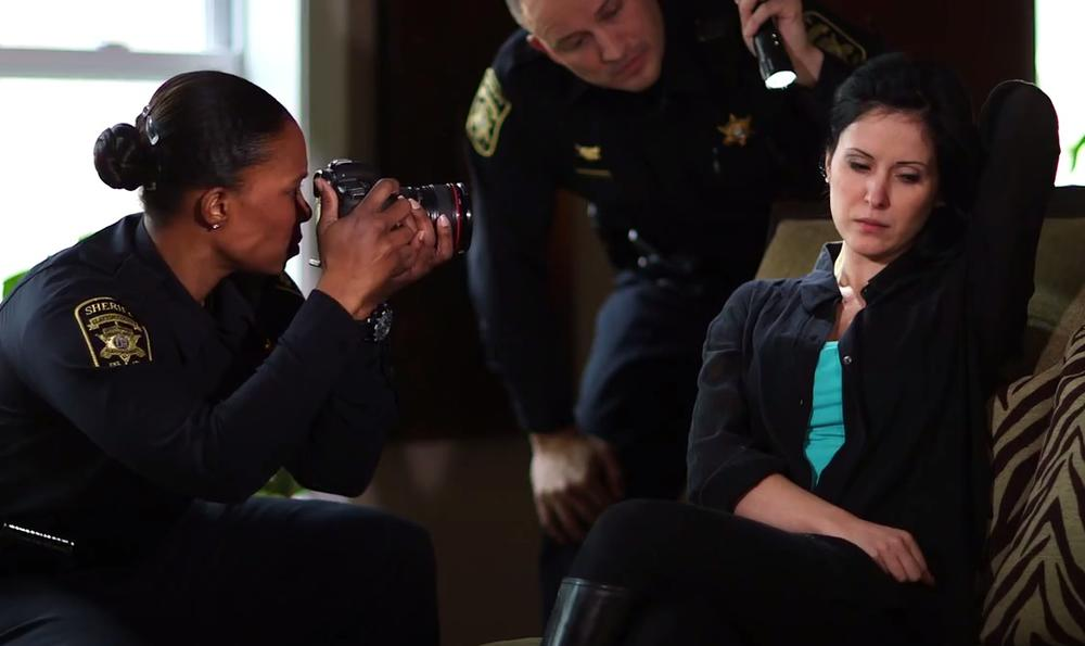 an image of a woman holding her hair back, a police officer shines a flashlight on her neck while another takes a photo.