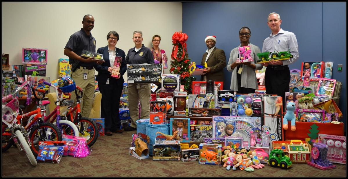 DCS staff members surrounded by donated toys